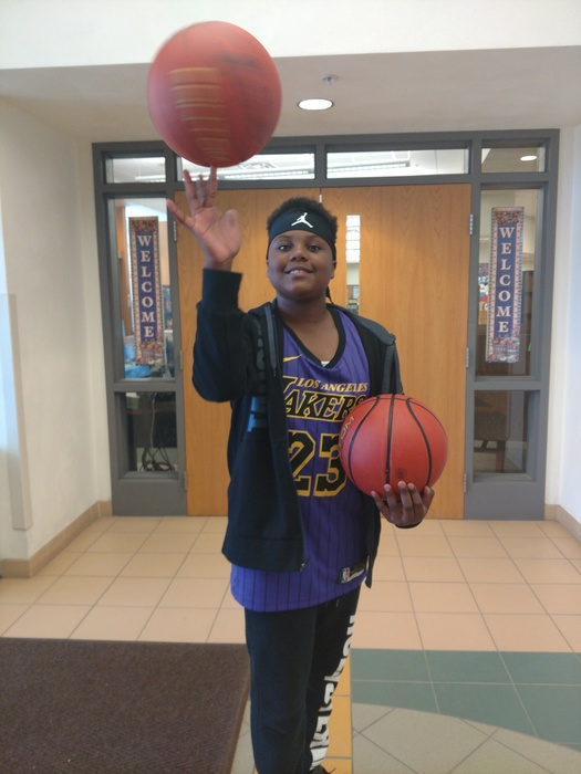 Student spins basketball on fingertip